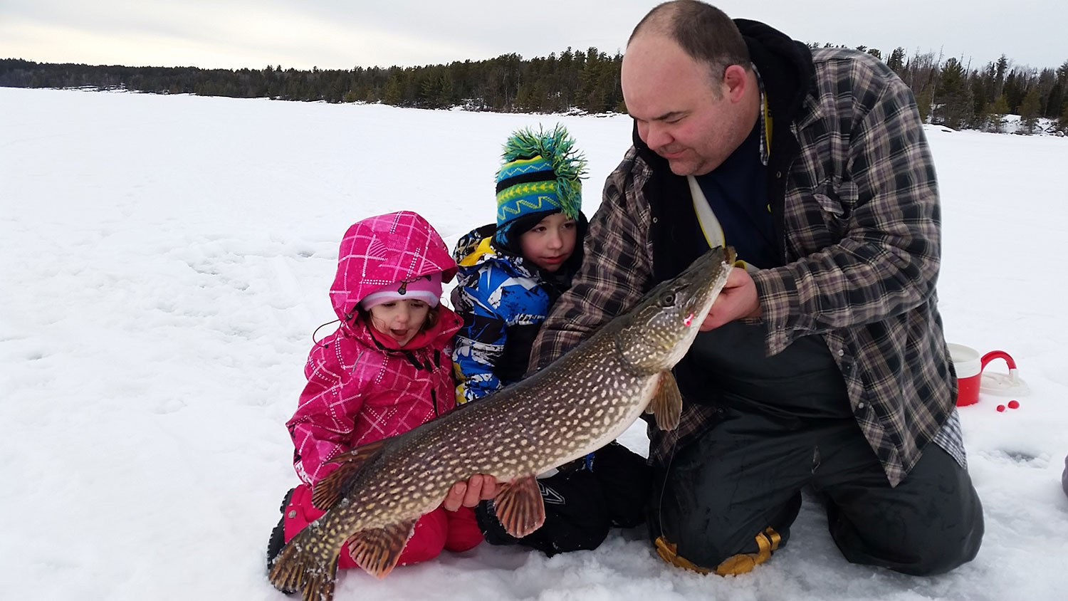 Brian Tucker on Rainy Lake with his two children holding a fish